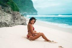 Ragazza castana con capelli ricci in un bikini rosso sulla spiaggia con la sabbia bianca vicino all'oceano sulla vacanza Un bello fotografia stock