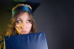 Ragazza castana con un diploma in costume di graduazione Fotografia Stock Libera da Diritti