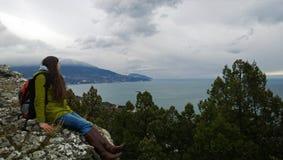 Ragazza castana con uno zaino che indossa un cappotto e gli stivali che si siedono su una roccia e che guardano verso il mare e l immagine stock libera da diritti