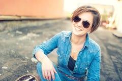 Ragazza castana d'avanguardia, sorridente e ridente contro il fondo arancio, isolato Ragazza del instagram dei pantaloni a vita b Fotografia Stock