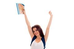 Ragazza castana felice alla moda dello studente con lo zaino blu e cartella per i taccuini in sua mano che esamina la macchina fo Immagine Stock Libera da Diritti