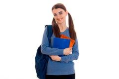 Ragazza castana felice alla moda dello studente con lo zaino blu e cartella per i taccuini in sue mani che esaminano la macchina  Immagine Stock Libera da Diritti