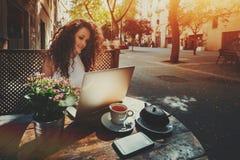 Ragazza castana riccia che lavora al computer portatile in caffè della via Fotografia Stock