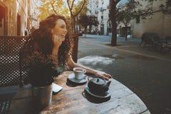 Ragazza castana riccia di risata in caffè della via Fotografia Stock Libera da Diritti