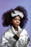 Ragazza castana riccia moderna vestita di un in un rivestimento colorato d'argento che indossa sulla sua testa le pose di vetro d fotografia stock