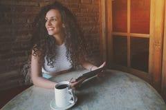 Ragazza castana riccia pensierosa con la compressa digitale in caffè Immagine Stock Libera da Diritti
