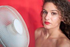 Ragazza castana sexy con capelli ricci con la ventola di raffreddamento immagine stock libera da diritti
