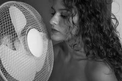 Ragazza castana sexy con capelli ricci con la ventola di raffreddamento fotografia stock libera da diritti