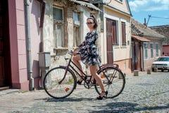 Ragazza castana sexy giovane con la vecchia retro bicicletta dell'annata di stile fotografia stock