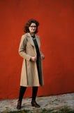 Ragazza castana snella in cappotto beige con gli occhiali al wa marrone rossiccio fotografie stock libere da diritti