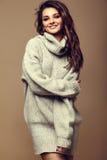 Ragazza castana sorridente sveglia della donna in maglione grigio caldo dei pantaloni a vita bassa casuali Immagine Stock