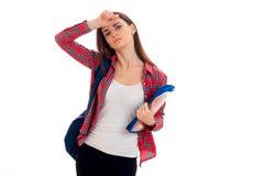 Ragazza castana stanca alla moda dello studente con lo zaino blu e cartella per i taccuini in sue mani che esaminano la macchina  Immagini Stock Libere da Diritti