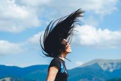 Ragazza castana sulla cima della montagna con il flusso continuo dei capelli fotografia stock libera da diritti