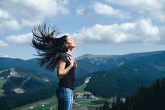 Ragazza castana sulla cima della montagna con il flusso continuo dei capelli fotografia stock