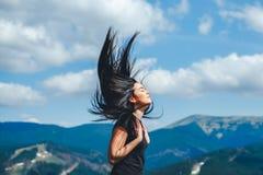 Ragazza castana sulla cima della montagna con il flusso continuo dei capelli immagine stock libera da diritti