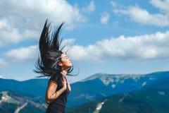 Ragazza castana sulla cima della montagna con il flusso continuo dei capelli fotografie stock