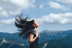 Ragazza castana sulla cima della montagna con il flusso continuo dei capelli fotografie stock libere da diritti