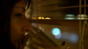 Ragazza castana sveglia che fa una pausa la finestra alla notte, spingendo i ciechi, esaminanti le luci notturne, sbadigli che la fotografia stock