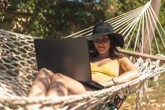 Ragazza castana in un costume da bagno giallo che si siede in un'amaca facendo uso di un computer portatile, lavoro sulla vacanza immagine stock libera da diritti