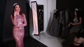 Ragazza castana in vestito brillante rosa, con una corona, un tiro di foto nello studio stock footage