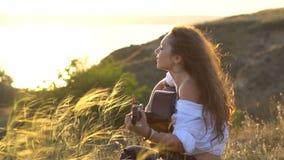 Ragazza castana zingaresca riccia che gioca chitarra e che canta nel campo sul pendio del golfo archivi video