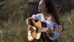 Ragazza castana zingaresca riccia che gioca chitarra e che canta nel campo sul pendio del golfo video d archivio