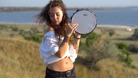 Ragazza castana zingaresca riccia che gioca sul tamburino nel campo sul pendio del golfo archivi video