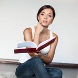 Ragazza casuale che si siede con il libro Fotografia Stock