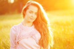 Ragazza casuale della giovane dei pantaloni a vita bassa donna del modello nel campo nel tramonto in spri Immagini Stock