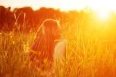 Ragazza casuale della giovane dei pantaloni a vita bassa donna del modello nel campo nel tramonto in spri Immagine Stock Libera da Diritti