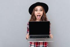 Ragazza casuale emozionante in camicia di plaid che tiene il computer portatile dello schermo in bianco Fotografie Stock Libere da Diritti