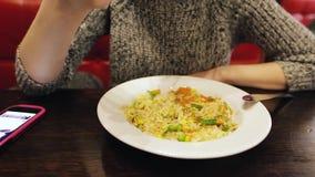 Ragazza caucasica attraente che mangia riso tailandese con le verdure in un caffè facendo uso dello smatphone archivi video