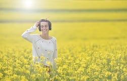 Ragazza caucasica che ascolta la musica con la cuffia nell'aria aperta Immagini Stock