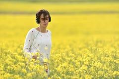 Ragazza caucasica che ascolta la musica con la cuffia nell'aria aperta Fotografia Stock