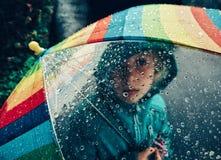Ragazza caucasica che guarda tramite l'ombrello dell'arcobaleno con le grandi gocce di pioggia fotografie stock libere da diritti