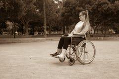 Ragazza caucasica con gli occhiali di protezione su una sedia a rotelle Ragazza triste danneggiata in un parco immagine stock libera da diritti