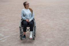 Ragazza caucasica con gli occhiali di protezione su una sedia a rotelle Ragazza triste danneggiata in un parco fotografia stock