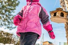 Ragazza caucasica del ittle sveglio in rivestimento di inverno di sport divertendosi gioco all'aperto con la neve Alimentatore de immagini stock libere da diritti