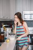 Ragazza caucasica della donna con capelli lunghi che cucina i pancake dell'alimento che stanno nella cucina Immagine Stock Libera da Diritti
