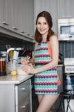 Ragazza caucasica della donna con capelli lunghi che cucina i pancake dell'alimento che stanno nella cucina Immagine Stock