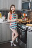 Ragazza caucasica della donna con capelli lunghi che cucina i pancake dell'alimento che stanno nella cucina Fotografia Stock Libera da Diritti