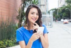 Ragazza caucasica di risata con il messaggio di battitura a macchina della camicia blu al telefono Fotografie Stock