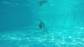 Ragazza caucasica nelle nuotate del bikini che girano sotto l'acqua alla macchina fotografica in stagno blu Vista da underwater video d archivio