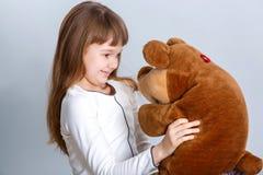 Ragazza che abbraccia orso Immagine Stock