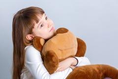 Ragazza che abbraccia orso Fotografia Stock