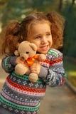 Ragazza che abbraccia un orso di orsacchiotto Immagini Stock Libere da Diritti