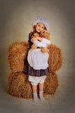 Ragazza che abbraccia un orso vicino al fieno Fotografia Stock