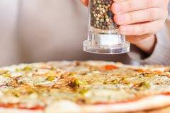 Ragazza che aggiunge le spezie sopra la pizza fotografia stock