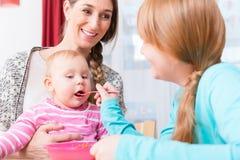 Ragazza che alimenta il suo bambino del fratello con il cucchiaio fotografia stock libera da diritti