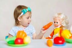Ragazza che alimenta una bambola a casa nella stanza del ` s dei bambini Immagini Stock